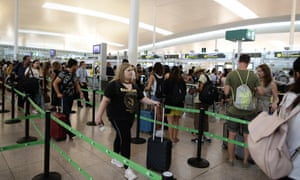 Passengers wait to pass security control at the Barcelona airport.
