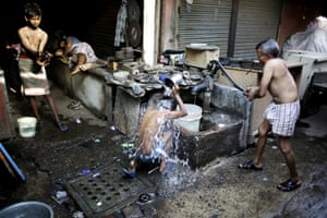Workers bath at a public tube well on a hot morning in Delhi