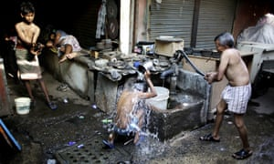 Indian migrant daily wage workers bath at a public well