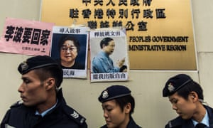 Police walk past notices about the missing booksellers.
