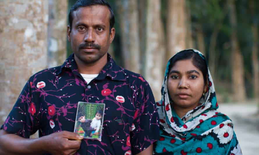 Shahanas Ackter and her husband Habibur Rahman with a picture of their son, Limon, who died aged eight, and his brother Yasin.