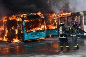 Firefighters extinguish a burning bus in Santiago