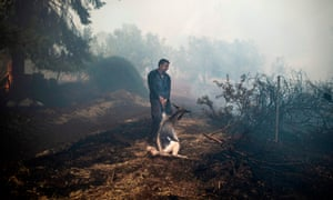 A farmer tries to save his goat during a major wildfire on the country's second-largest island, Evia, northeast of Athens