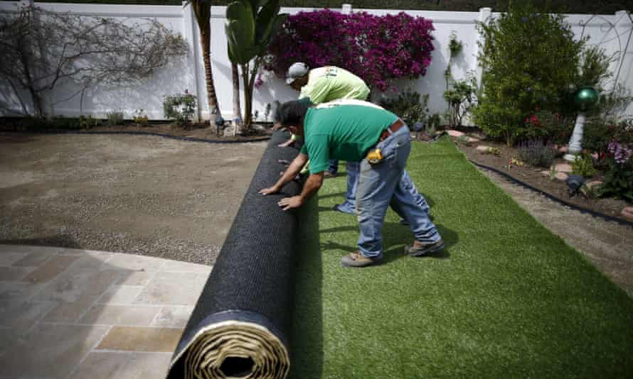 Workers roll out artificial turf after digging up a lawn due to the drought, at a home in Laguna Niguel, California.