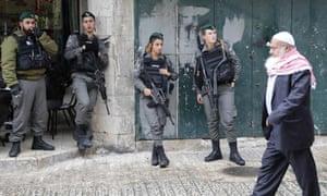A Palestinian man walks past Israeli border guards in Jerusalem's Old City