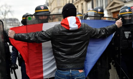 A protester confronts riot police at a Paris rally against Emmanuel Macron's proposed pension overhaul.