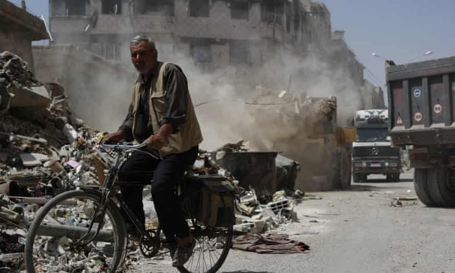 A man cycles past a bulldozer removing rubble, in the town of Douma near Damascus