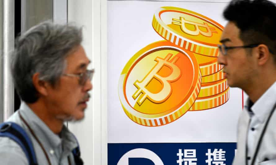 Pedestrians pass a bitcoin currency poster in Tokyo.