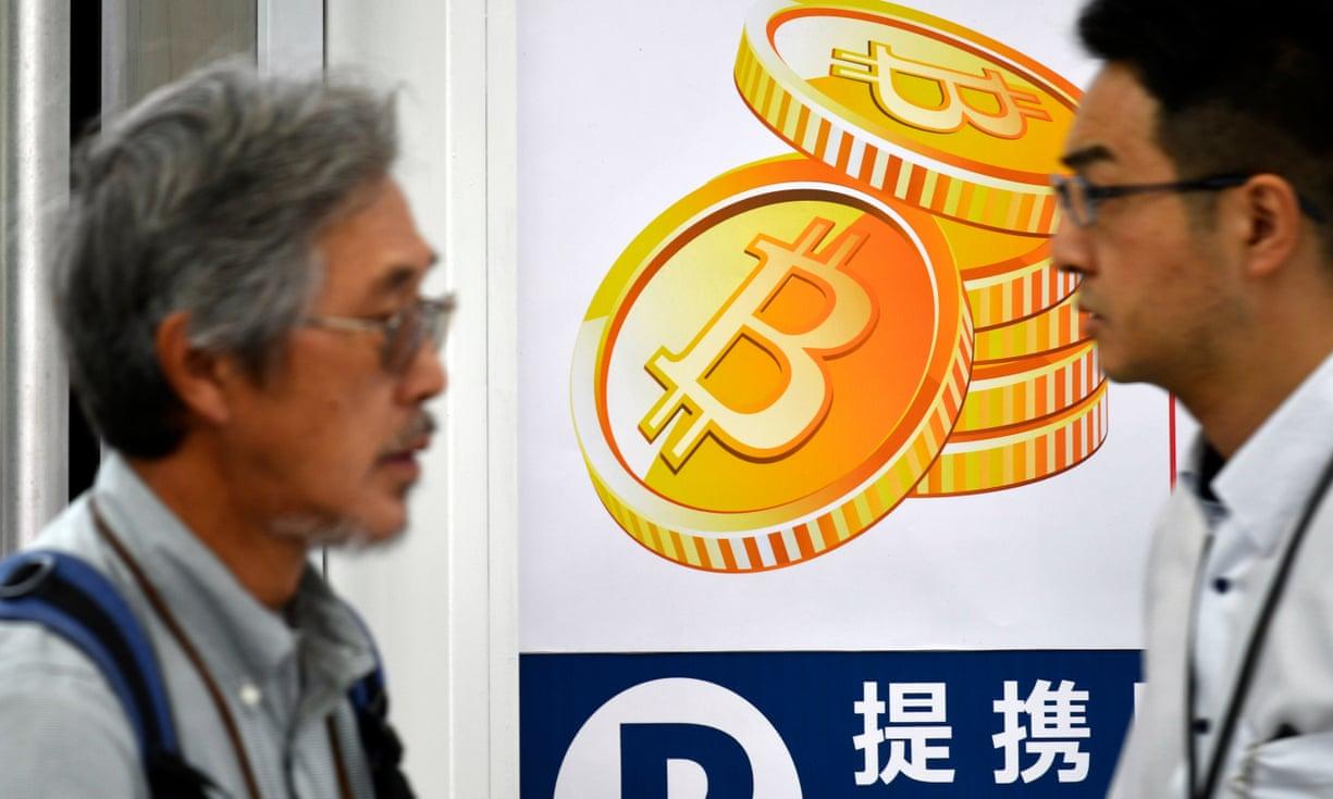 Жители Токио проходят мимо постера с изображением биткоина на входе в магазин электроники.