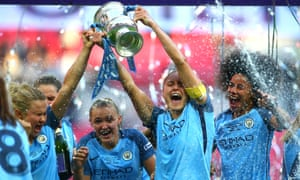 Steph Houghton, second right, and Isobel Christiansen of Manchester City Women celebrate with the trophy and their team-mates.