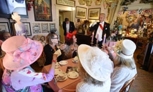 Edmund Fry leads guests in a toast to Prince Harry and Meghan Markle during afternoon tea at the Rose Tree Cottage in Pasadena, surrounded by cardboard cutouts of the royal family.