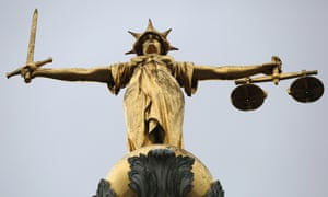 A statue of the scales of justice stands above the Old Bailey, London