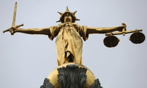 A statue of the scales of justice stands above the Old Bailey, London.