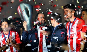 Evangelos Marinakis holds the Greek Championship trophy with Olympiacos in May last year.
