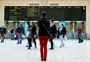 A traveller stands in front of an information board at a Belgian railway station.