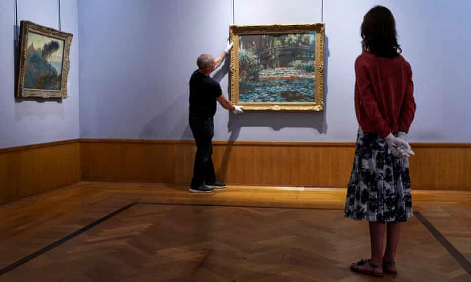 A Monet Waterlilies painting being hung at the Barber Institute of Fine Arts, University of Birmingham.