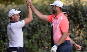 Jon Rahm celebrates after a hole-in-one on the 17th hole with his playing partner Danny Willett. The Spaniard shot a course-record 61 to sit four shots off the lead.