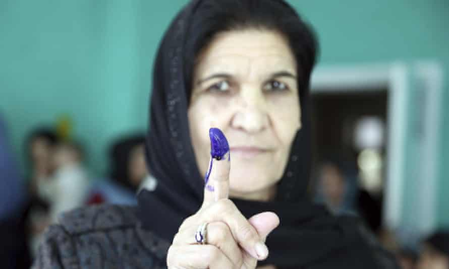 An Afghan woman shows her inked finger after in the parliamentary elections in 2018.