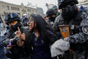 A female demonstrator is detained by riot police.