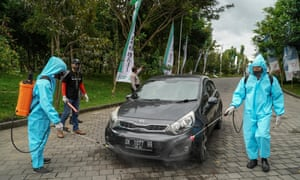 Workers spray a spectator's car with disinfectant at the first drive-in music concert in Bali, held in the Ubud region, amid the pandemic.