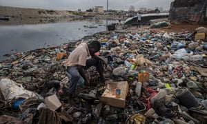 A fisherman looks for bait at a shanty town in the south of Luanda.
