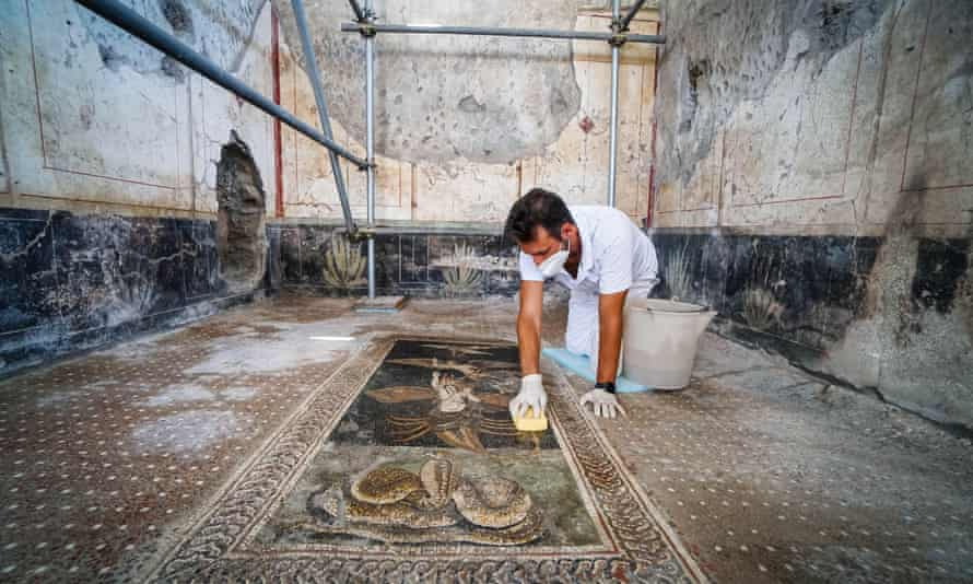A worker cleans a mosaic in a house next to the thermopolium which will also open.