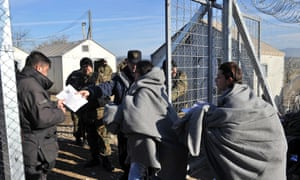 Border police check the documents of two migrants as they are allowed to cross the Greek-Macedonian border near Idomeni.