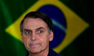 Brazil's right-wing presidential candidate for the Social Liberal Party (PSL) Jair Bolsonaro gestures in front of the Brazilian flag as he prepares to cast his vote during the general elections on October 7, 2018.