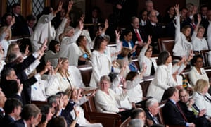 Female members of Congress wearing white, hold up three fingers for the HR3 health care bill as Donald Trump talks about healthcare during his State of the Union address.