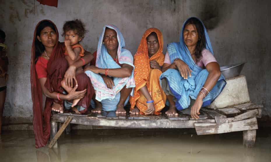 Urmila Devi, Sangeeta Devi, Marni Devi and Nago Devi sit on a bed raised just above the floodwaters in the village of Chajan Mania.
