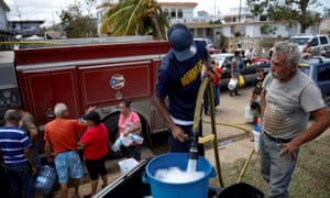 A fireman fills containers with water for residents in Toa Baja, Puerto Rico on Sunday.