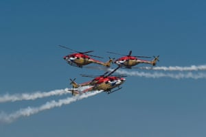 Three red helicopters in the sky with vapour trails