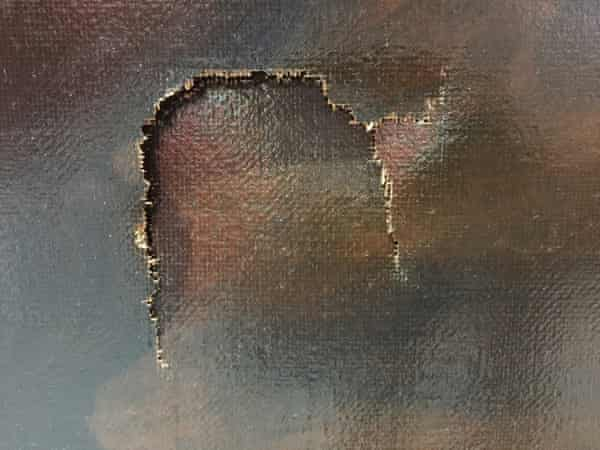 A close-up view of the puncture in the canvas.
