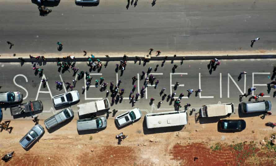A human chain is formed by aid workers, medical and rescue services in a vigil calling for the Bab al-Hawa crossing to be kept open, near Bab al-Hawa, 2 July