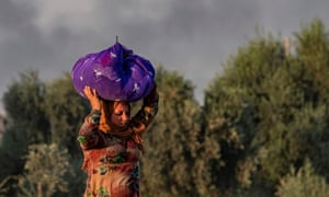 A woman carries her belongings over her head as she flees as the Turkish bombardment of Ras al-Ayn begins.