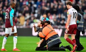 A pitch invader gestures at Angelo Ogbonna, West Ham v Burnley