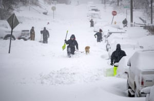 Neighbors work together in an effort to clear out as much snow as possible from East 8th Street Sunday in Duluth, Minnesota.