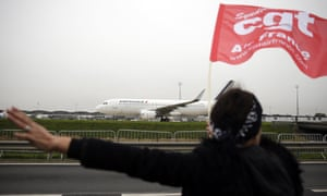 An Air France employee waves a CGT union flag