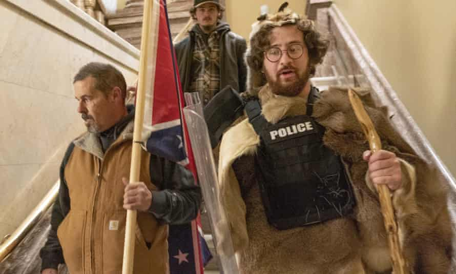 Aaron Mostofsky, right, seen inside the US Capitol wearing a police bulletproof vest and carrying a police shield, has been arrested on a felony count of theft of government property.