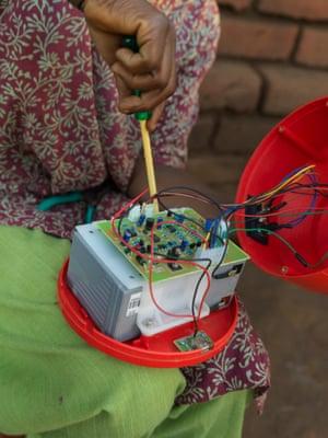 Emily Kamwendo repairs a solar-powered lamp