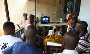 Men in Abidjan watch a live broadcast of the trial of Laurent Gbagbo at the international criminal court.