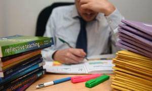 School teacher next to a pile of classroom books