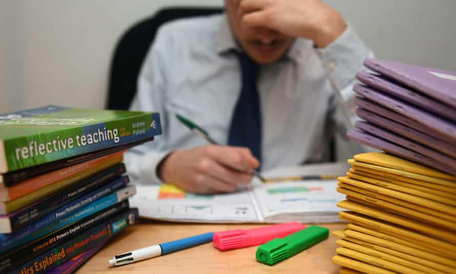 Teacher making notes at a desk