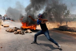 A Palestinian youth hurls a stone towards Israeli forces in the village of Turmus Aya following a protest march against the building of Israeli settlements.