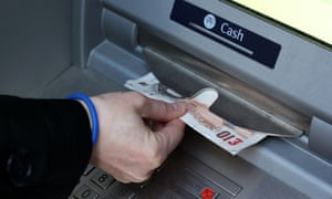Someone takes cash from a cash machine.