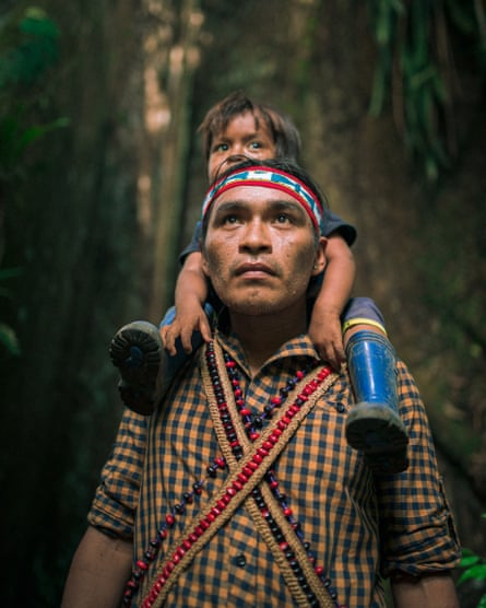 A member of the Achuar tribe with his child in the Amazon forest, Sharamenza, Ecuador.