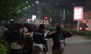 Police look on as an armoured car tackles gunmen who attacked a restaurant in Ouagadougou.