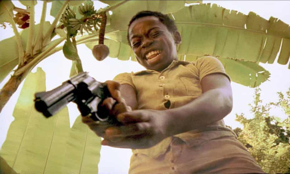 Film still City of God, lead character as a boy pointing a gun and laughing.