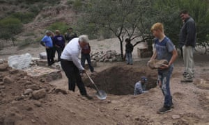 Men dig a mass grave for some of the women and children who died on Monday.