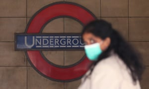 A woman wearing a face mask walks past Leicester Square Underground station in London.